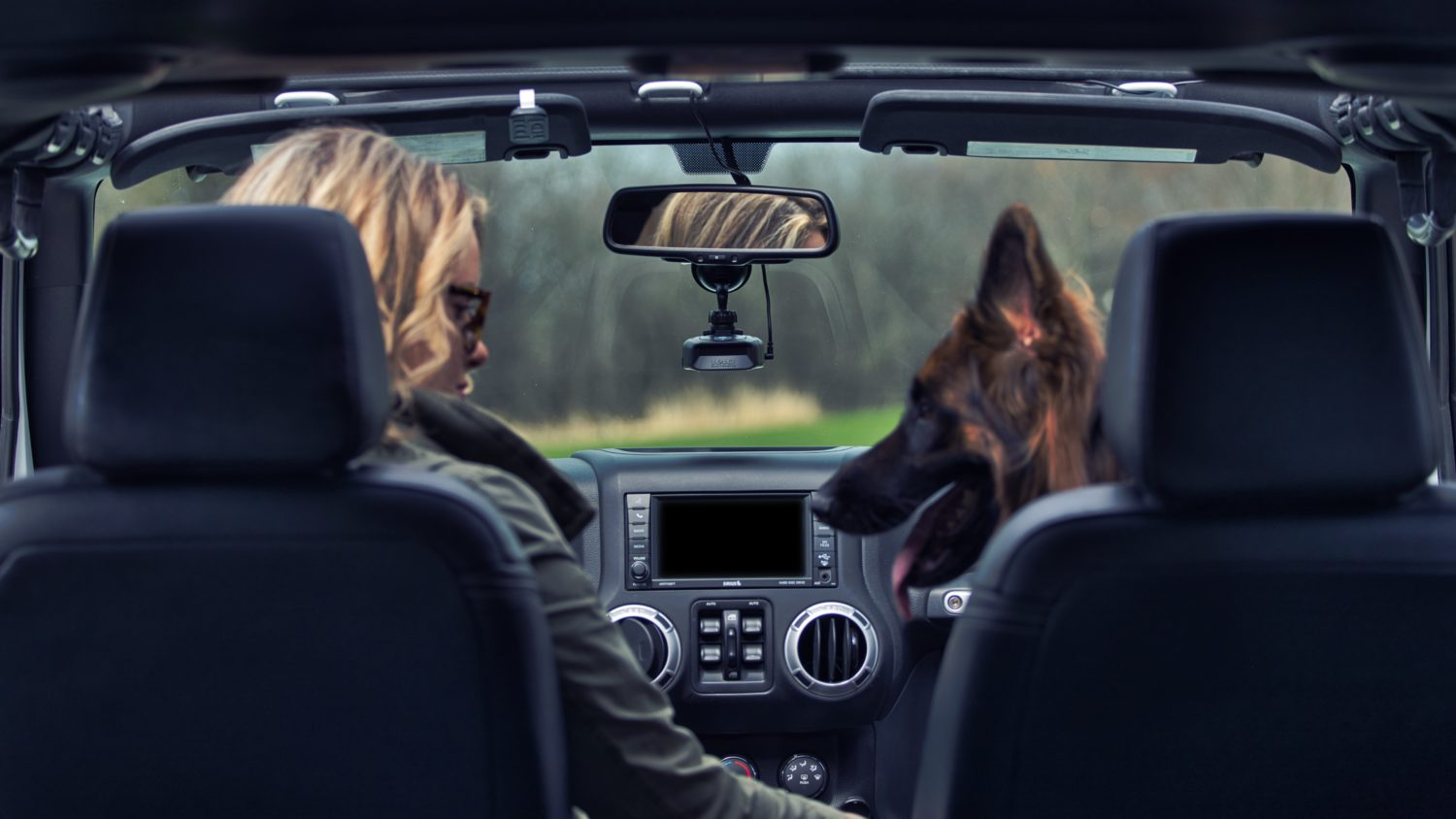 Woman in Jeep Wrangler driving with K40 Platinum100 and her German Shepard